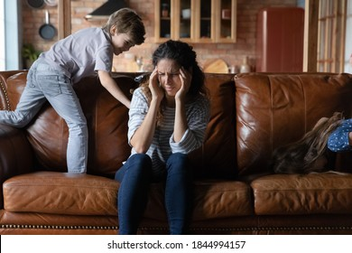 Unhappy young Caucasian mom suffer from headache stressed tired by naughty small 7s son playing. Upset exhausted mother feel distressed by ill-behaved naughty child kid, struggle from migraine.