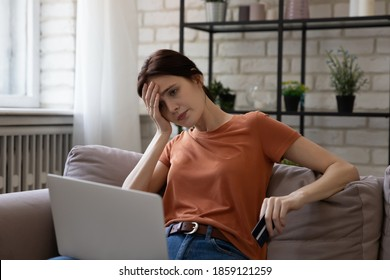 Unhappy young caucasian woman looking at computer screen, feeling stressed entering wrong payment information from credit card, having lack of money, financial problems or hacked bank account.