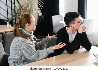 Unhappy young couple arguing, angry wife looking at husband blaming him of problems, conflicts in marriage, bad relationships, man and woman having quarrel or disagreement