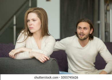 Unhappy young couple arguing, offended affronted woman ignoring angry man sitting her back to jealous husband shouting at frustrated wife, family fight at home, bad marriage relationships concept