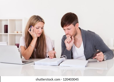 Unhappy young couple in financial trouble at home