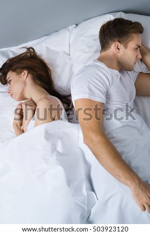 Unhappy young couple on the bed in bedroom. Caucasian models - in love crisis, relationship, frustrated concept shot.
