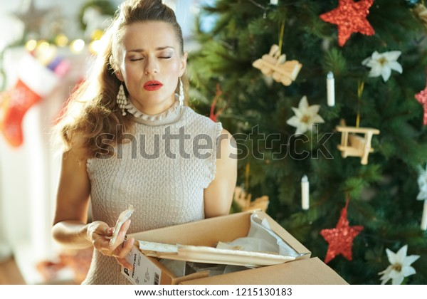 unhappy young housewife near Christmas tree pulling out a broken dish from the parcel