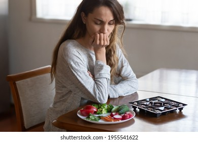Unhappy young Latin woman look at chocolates and vegetables face temptation suffer from eating disorder. Millennial female think of healthy food choice, diet. Wellbeing, weight loss concept.