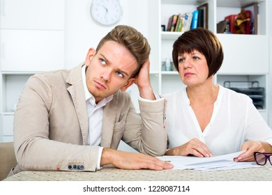 Unhappy young man and mature woman sit at table and discuss legal aspects of paperwork. Focus on the man