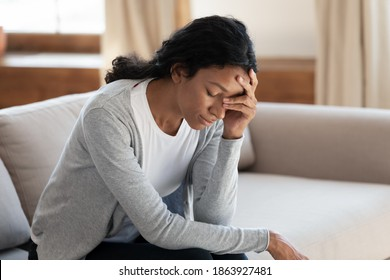 Unhappy young woman feel distressed frustrated at home, suffer from miscarriage or abortion. Upset sad millennial African American female struggle with mental personal or health problems.