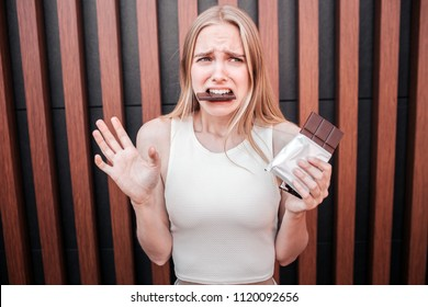 Unhappy young woman is holding a chocolate bar in hand and eating big piece at the same time. She feels guilty for eating it. Isolated on striped background.