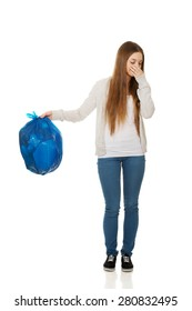 Unhappy young woman holding a full garbage bag.