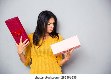 Unhappy young woman holding gift box over gray background