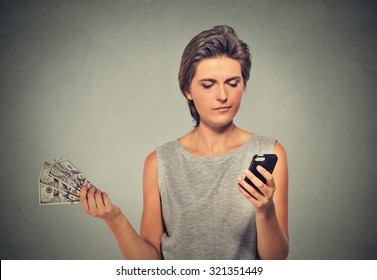 Unhappy young woman looking at smart phone throwing away cash dollar bills isolated on gray wall background. Angry upset face expression. Making spending money financial reward compensation concept