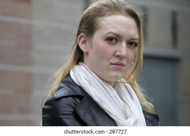 Unhappy young woman looks at the viewer