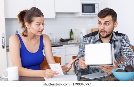 Unhappy young woman and man with box of purchase having conflict at home