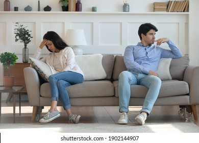 Unhappy young woman and man not talking after quarrel, sitting on couch separately back to back, frustrated wife and husband ignoring each other, relationship problem, family crisis concept
