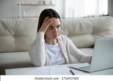 Unhappy young woman sit at home work on laptop frustrated by slow Internet connection on gadget, upset distressed female have operational computer problems, stressed by unpleasant email or message