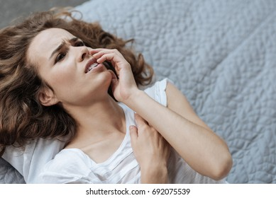 Unhappy young woman suffering from the toothache