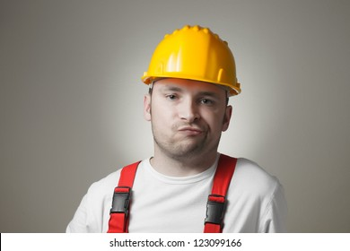 Unhappy young worker with yellow hard hat