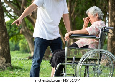 Unhappy,problems asian family,angry man or male caregiver expelled his elderly woman in wheelchair quarrel,arguing,senior mother crying in outdoor,aggressive son,family,violence,ungrateful concept