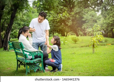 Unhappy,problems asian family,husband pointing at wife blaming her quarreling,parents quarrel,arguing child girl listen,mother,daughter sad,crying,aggressive father,family conflict,violence in outdoor