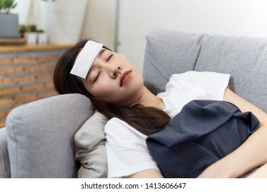 Unhealthy Asian beautiful girl has a fever closing her eyes sleeping on sofa at home. She put fever cooling patch on her forehead and covered herself with a blanket. Illness and sickness concept.