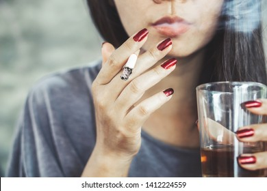 unhealthy Asian woman hand smoking cigarette and drinking glass of alcohol