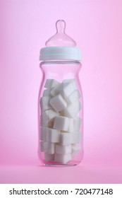Unhealthy baby food concept. Baby bottle filled with white sugar cubes to highlight hidden sugar in children's drinks.