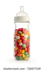 Unhealthy baby food concept. Isolated baby bottle filled with colorful candies to highlight the excess of sugar in children's diet.