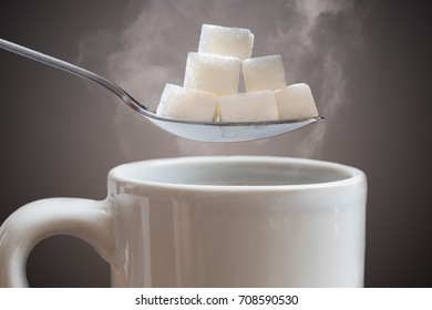Unhealthy eating concept. Many sugar cubes above hot cup of tea or coffee.
