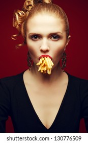 Unhealthy eating. Junk food concept. Arty portrait of fashionable young woman holding (eating) fried potato in her mouth and posing over red background. Studio shot