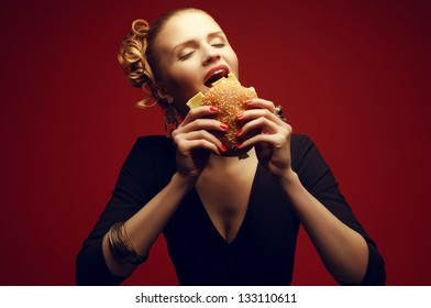 Unhealthy eating. Junk food concept. Guilty pleasure. Portrait of happy fashionable model holding burger and posing over red background. Perfect hair, skin, make-up and manicure. Studio shot