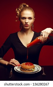 Unhealthy eating. Junk food concept. Portrait of fashionable young woman holding bottle with tomato sauce, pouring it and going to eat burger. Perfect hair, skin, make-up and manicure. Studio shot