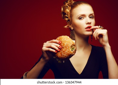 Unhealthy eating. Junk food concept. Portrait of fashionable young woman holding burger and posing over red background. Copy-space. Perfect hair, skin, make-up and manicure. Studio shot