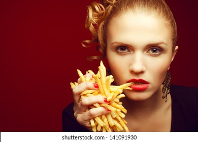 Unhealthy eating. Junk food concept. Portrait of fashionable young woman holding (eating) fried potato (fries, chips) in her hand and posing over red background. Close up. Copy-space. Studio shot