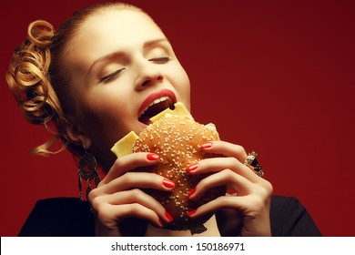Unhealthy eating. Junk food concept. Guilty pleasure. Portrait of happy fashionable model holding burger & eating over red background. Perfect hair, skin, make-up & manicure. Copy-space. Studio shot