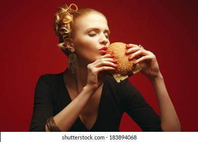 Unhealthy eating. Junk food concept. Guilty pleasure. Fashionable hipster girl holding & eating cheeseburger over red background. Perfect hair, skin, make-up & manicure. Copy-space. Studio shot