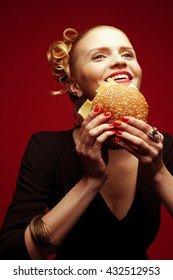 Unhealthy eating. Junk food concept. Guilty pleasure. Happy fashionable hipster girl in black dress holding cheeseburger over red background. Perfect hairdo, skin, make-up & manicure. Studio shot