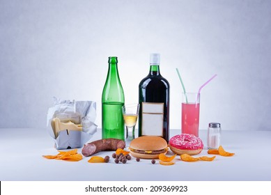 Unhealthy and fat food composition of butter, alcoholic drinks, salt, crisps, hamburger, sausage, donut, candies and colored soda drink.