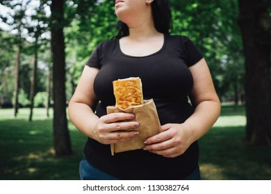 Unhealthy fattening food,high-calorie snack, eating on the go, take-out meals. Overweight woman eating doner kebab walking in the street