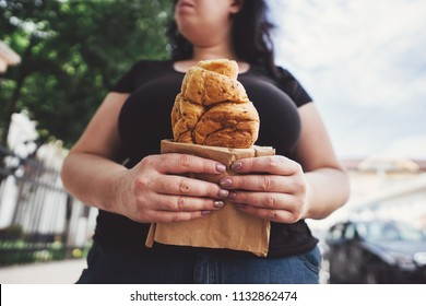 Unhealthy fattening food,high-calorie snack, eating on the go, take-out meals. Overweight woman eating croissant walking in the street