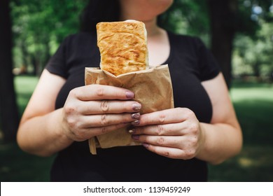 Unhealthy fattening food,high-calorie snack, eating on the go, take-out meals. Overweight woman eating shawarma walking in the street