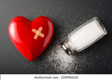 Unhealthy food concept - salt. Heart and salt shaker on dark background