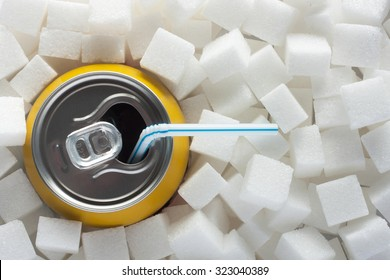 Unhealthy food concept - sugar in carbonated drink. Sugar cubes as background and canned drink with straw drink