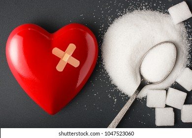 Unhealthy food concept - sugar. Spoon with sugar and heart with bandage