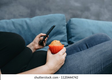 Unhealthy food, mindless snacking, sedentary lifestyle, compulsive overeating. Obese woman laying on sofa with smartphone eating sweets.