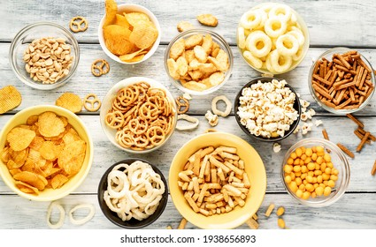 Unhealthy food. pretzels, various chips, croutons, cookies in bowls. unhealthy food for figure, heart, skin, teeth. An assortment of fast carbohydrates. On a wooden background