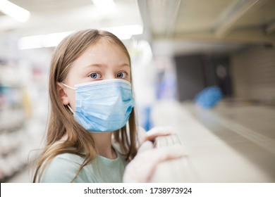 Unhealthy girl in medical mask looking or choosing medicine in the pharmacy during pandemic corona virus. Empty shelf in the store – deficit.