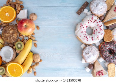 Unhealthy and healthy sweets on blue wooden background. Organic and dietary food and the problem of refusal from harmful desserts. Fruits and nuts vs donuts cupcakes and candy