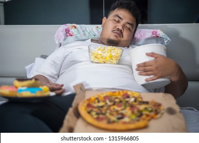Unhealthy lifestyle concept: Asian obese man eating junk foods during sleeping on the bed