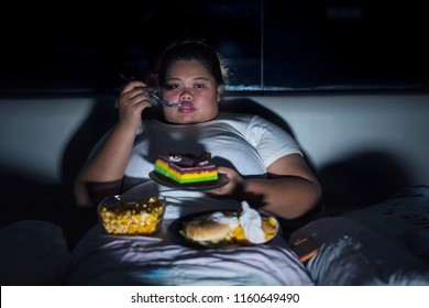 Unhealthy lifestyle concept: Overweight woman eating junk food in bed before sleeping