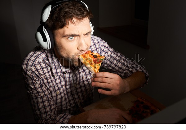 Unhealthy lifestyle. Junk food, fast food.Sloe up portrait of young bearded male gamer with short hair in casual shirt and headphones, playing online games in night, sloppily eating slice of pizza