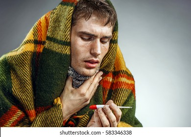 Unhealthy man suffering from sore throat. Photo of sick man wrapped in blanket with thermometer.